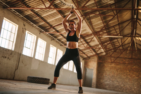 Strong woman exercising with battle rope
