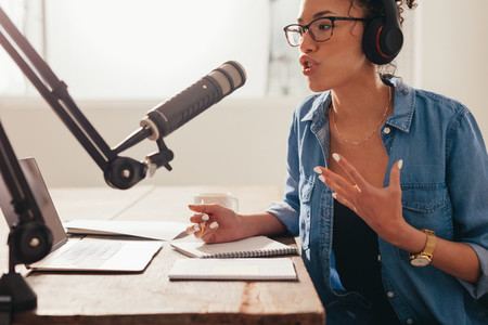 Woman recording and broadcasting her podcast from home