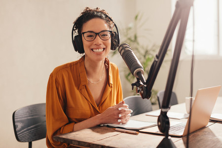 Cheerful woman recording a podcast from home