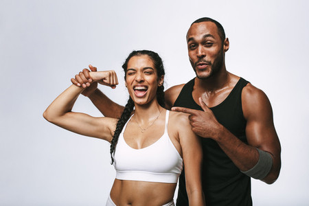 Fit couple having fun showing biceps