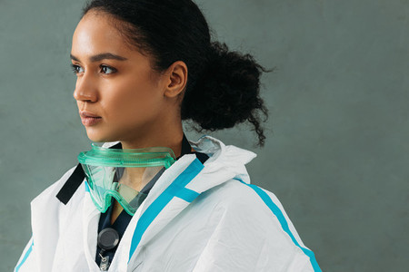 Young serious nurse in a protective suit with glasses