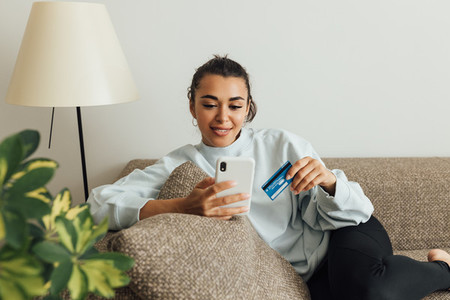 Woman in casual clothes relaxing on the sofa making online order