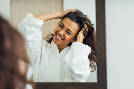 Happy brunette woman with palms in her hair looking at mirror reflection