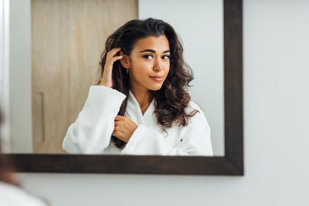 Beautiful female wearing bathrobe looking at a mirror