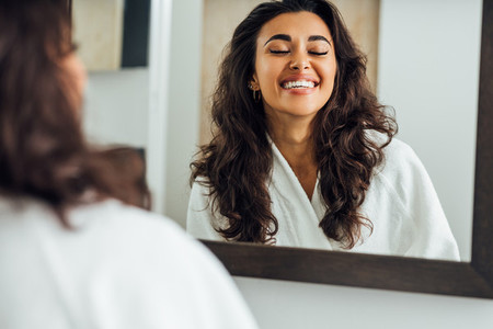 Happy woman with closed eyes standing in front of a mirror