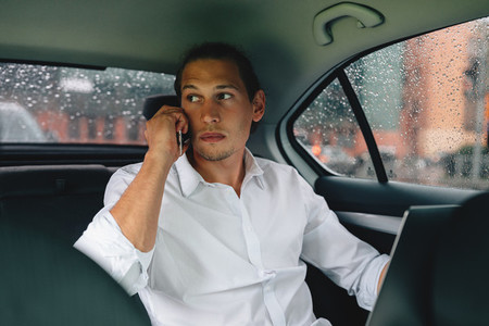 Young businessman sitting on a backseat of a taxi