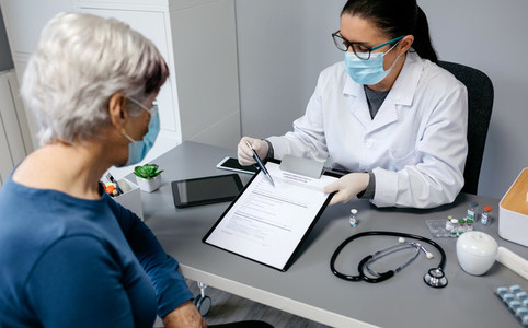 Doctor explaining to her patient consent form to coronavirus vaccine