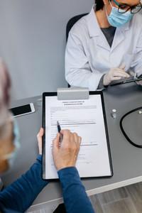 Woman reading consent form for coronavirus vaccine