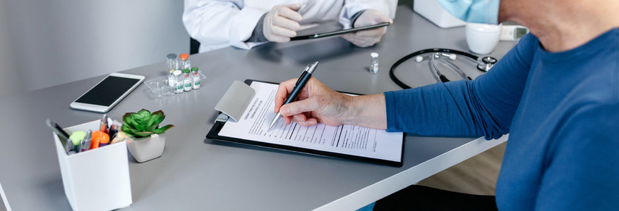 Woman filling in consent form for coronavirus vaccine