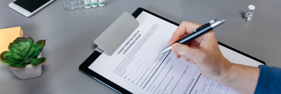 Unrecognizable woman filling in consent form for coronavirus vaccine