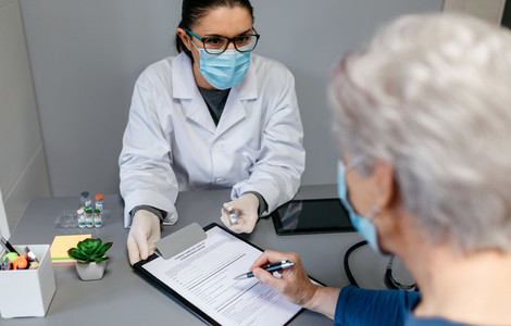 Doctor explaining to her patient the benefits and risks of the coronavirus vaccine