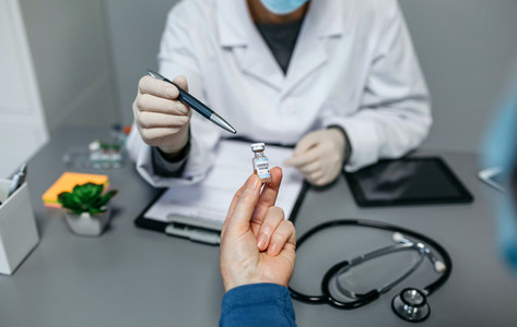Unrecognizable doctor explaining to her patient the benefits and risks of the coronavirus vaccine