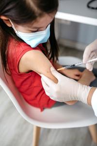 Girl receiving coronavirus vaccine at doctors office