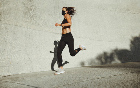 Sportswoman with face mask on morning run