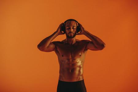 Portrait of muscular athlete enjoying music