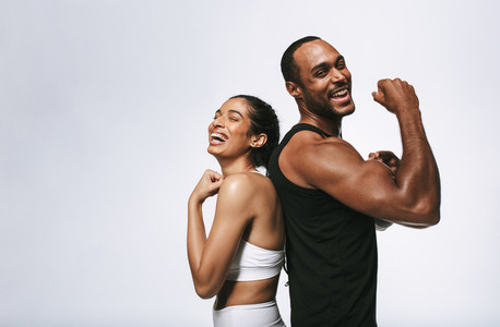 Cheerful fit couple on white background