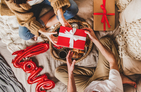 Unrecognizable couple sitting in bed and giving presents