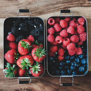 Fresh berries in metal lunchboxes over wooden background square crop