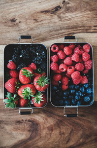 Fresh berries in metal lunchboxes over wooden background copy space