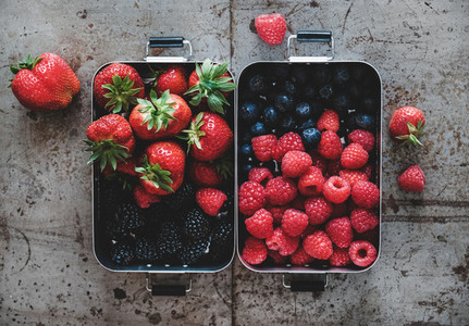 Flat lay of fresh berries in lunchboxes over rough grey background