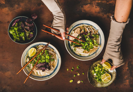 Womans hands with chopsticks and lime over vietnamese Pho Ga soup