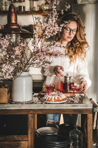 Young woman serving homemade bundt cake and tea in kitchen