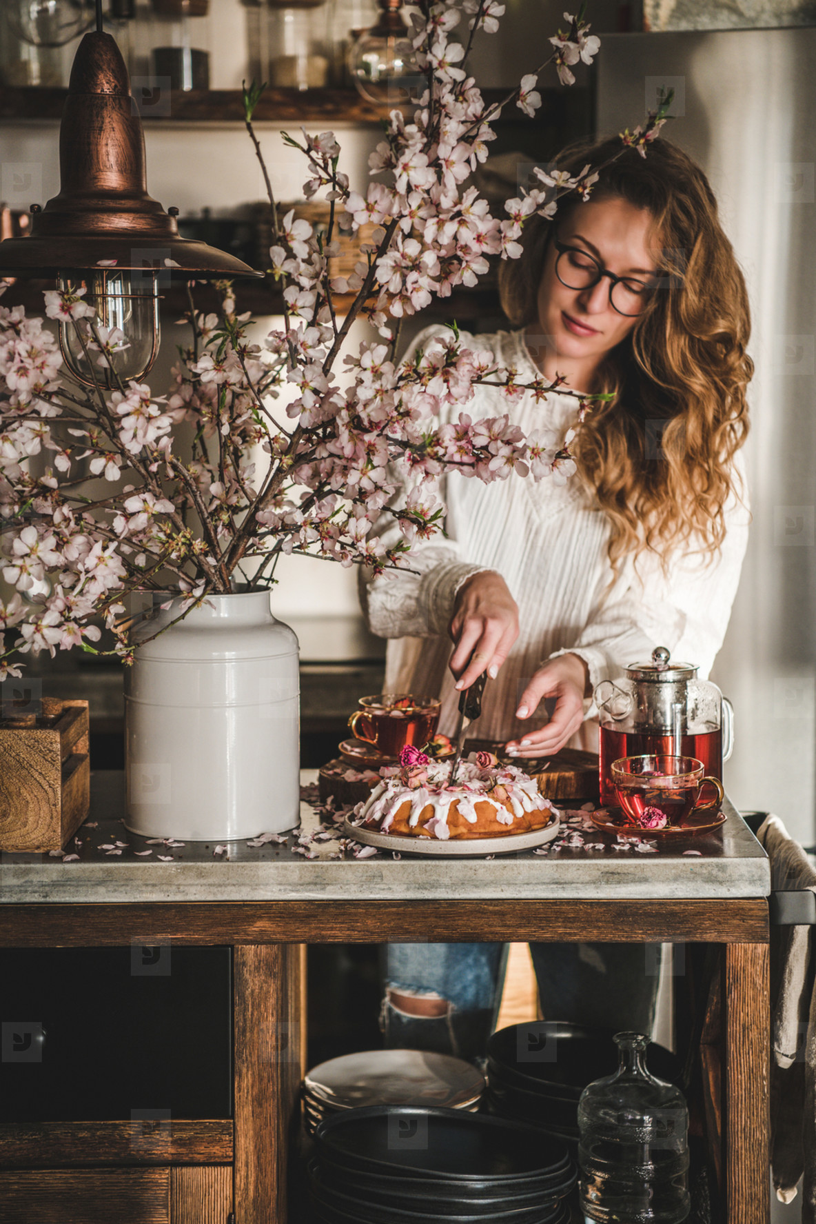 Woman cutting homemade gluten free bundt cake near blooming branches