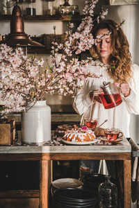 Young woman pouring tea over table with spring bundt cake