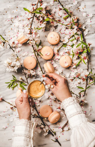 Womans hands holding fresh coffee over macaron cookies and flowers