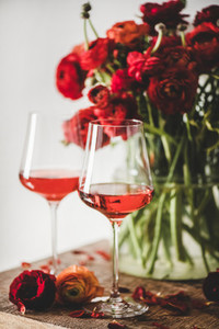 Rose wine in glasses and red spring flowers selective focus