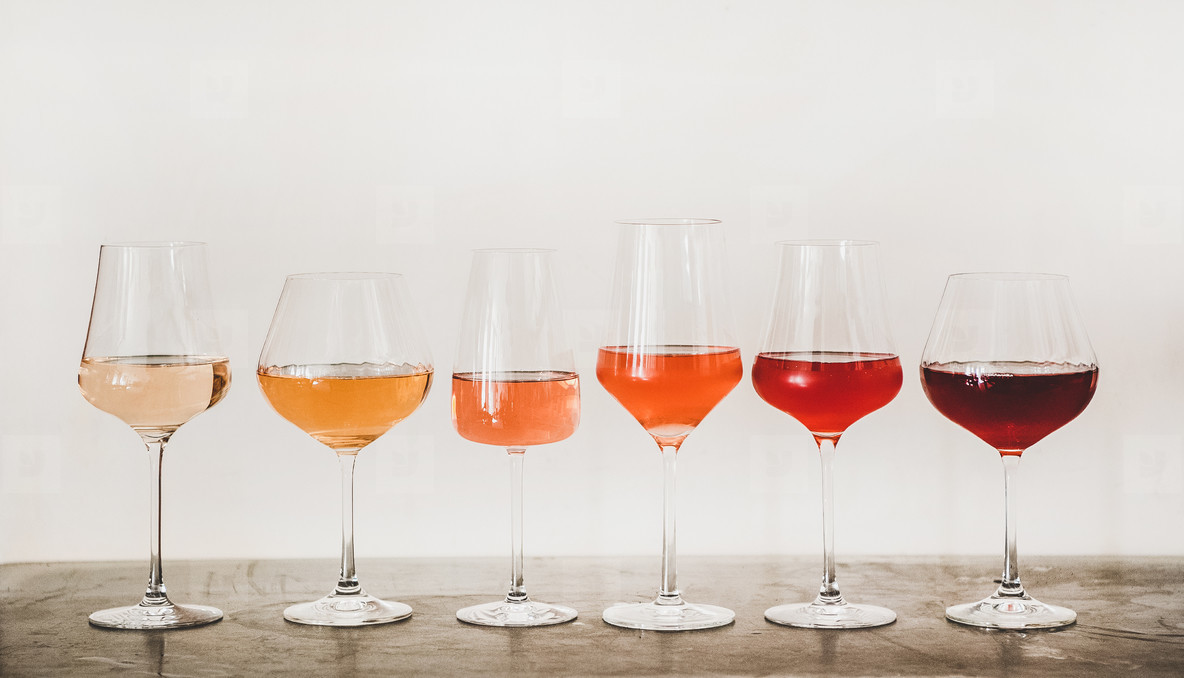 Shades of Rose wine in glasses on concrete table