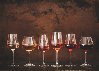 Shades of Rose wine in glasses  rusty background  copy space
