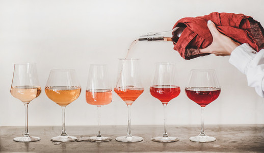 Rose wine glasses and womans hand pouring wine  white background