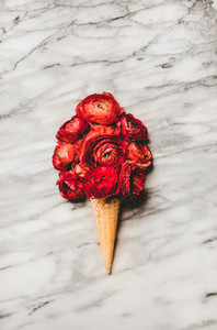 Ice cream waffle cone with scoop of red ranunculus flowers
