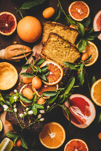 Citrus Mediterranean loaf cake with fresh fruits over rusty background