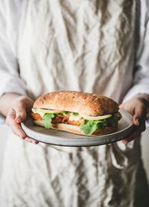 Woman in linen apron holding breakfast sandwich with fried fish