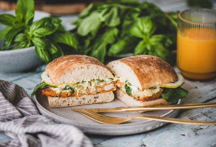 Breakfast with fish sandwich  fresh greens and orange juice