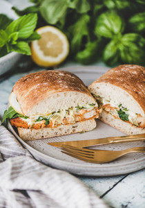 Breakfast with fish sandwich filled with lemon and greens