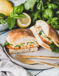 Fish sandwich filled with lemon and greens cut in halves