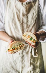 Woman holding fried fish sandwich with tartsre sauce  lemon  arugula