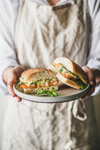 Woman holding plate with fresh fried fish sandwich with lemon
