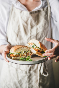 Woman holding plate with fresh fried fish sandwich in halves