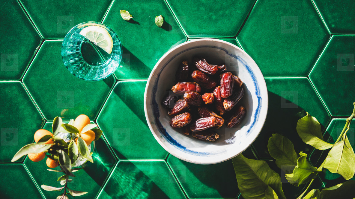 Flat lay of Islamic Ramadan Iftar food over green tile table