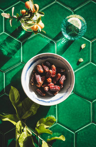 Flat lay of Islamic Ramadan Iftar food over green tile