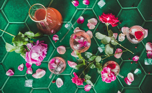 Rose lemonade with ice and petals over green table