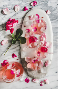 Rose lemonade with ice and rose petals over marble background