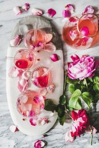 Rose lemonade with ice and fresh roses over marble background