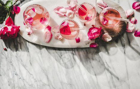 Rose lemonade with ice and fresh rose petals  copy space