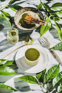 Green matcha cheesecake on plate and green plant leaves