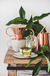 Green matcha cheesecake and black coffee in copper pot